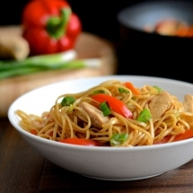 A bowl of homemade chicken chow mein with a wok and chopping board of ingredients in the background.
