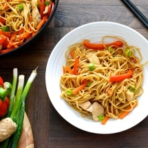 Looking down of a bowl of chicken chow mien. Next to the bowl is more chow mein in a wok and some of the ingredients on a chopping board - spring onions, red pepper and garlic.