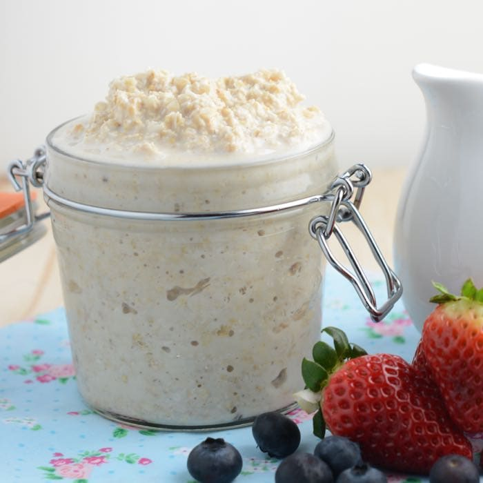 A jar full to the brim with overnight oats made with just milk and oats next to a milk jug and some fresh fruit.