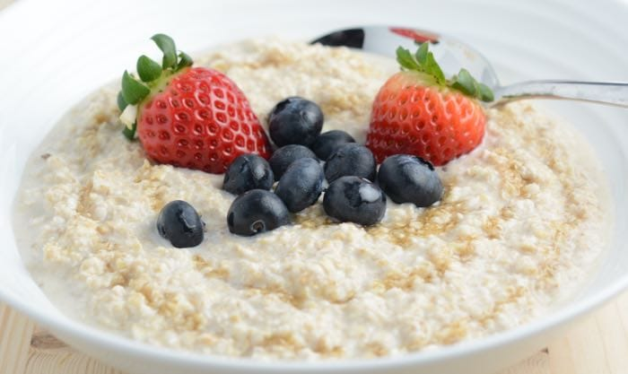 A bowl of overnight oats topped with maple syrup and fresh fruit.