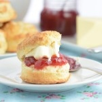 A plain afternoon tea scone filled with strawberry jam and clotted cream. In the background there's a stack of scones, a jar of strawberry jam and a block of butter.