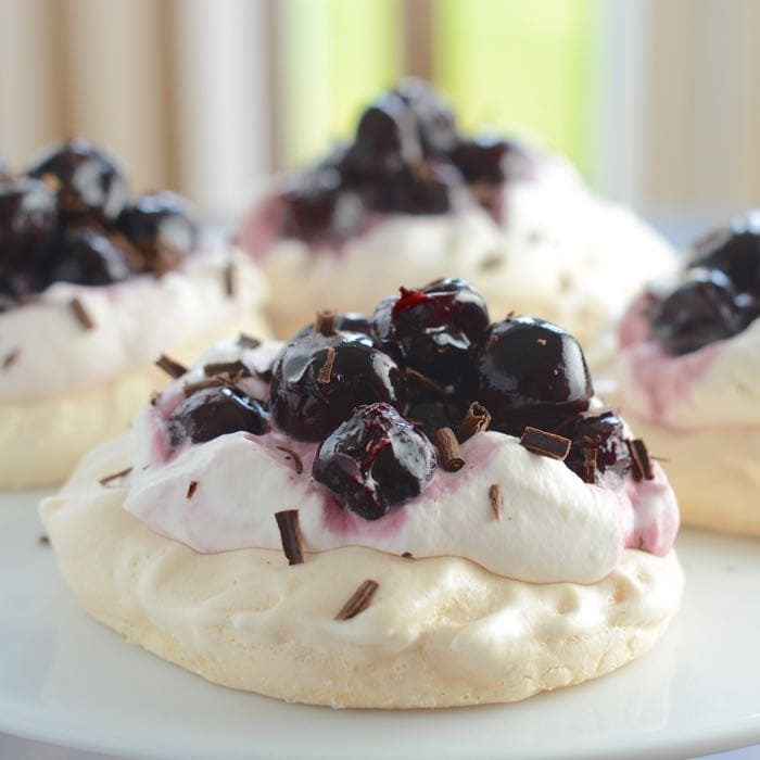 A delicious, indulgent, grown-up dessert recipe - Crisp meringue topped with whipped cream, kirsch soaked cherries and chocolate shavings.