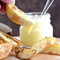 A potato wedges that just been dipped in mayonnaise. There's more wedges on a board and a jar of mayonnaise in the background.