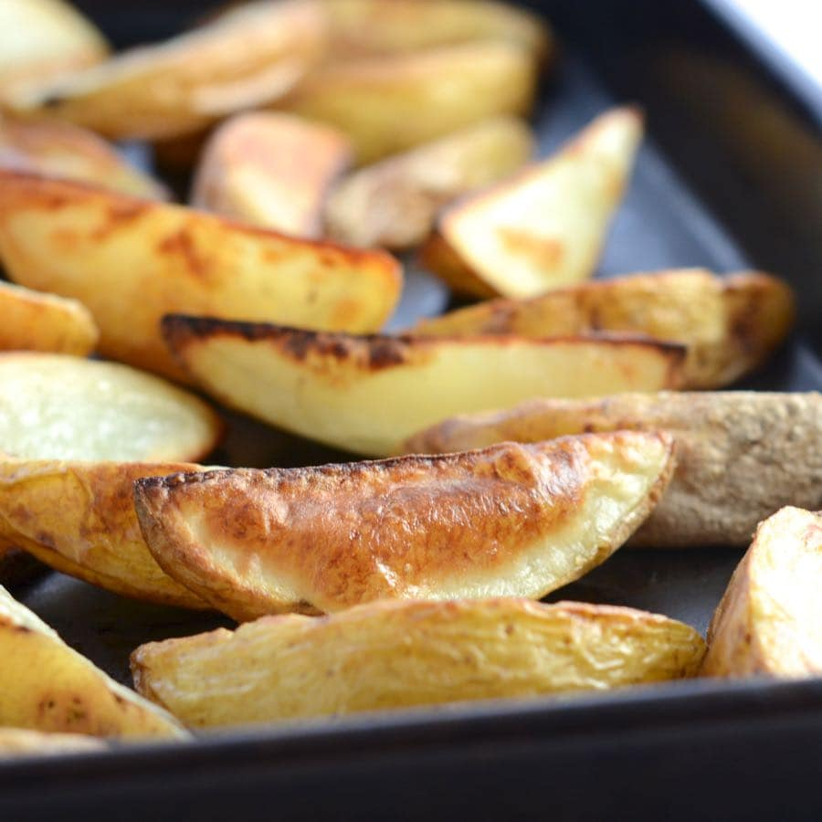 Homemade potato wedges in a baking tray.