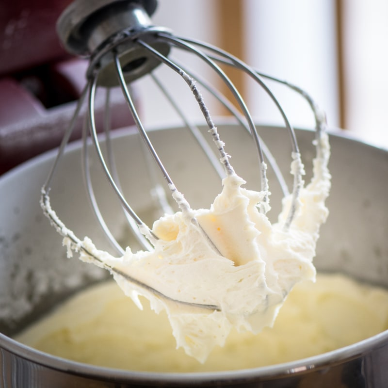 A stand mixer whisk covered in vanilla buttercream.