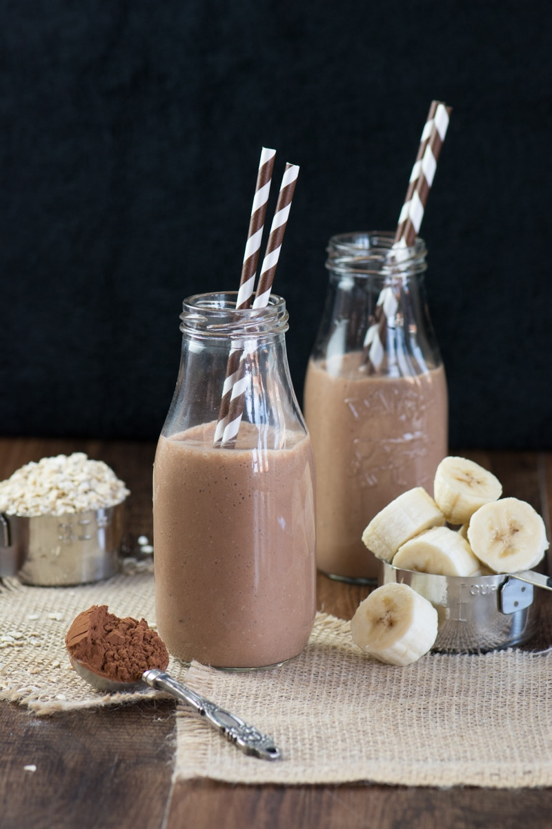 Two glass milk bottles filled with a coconut, banana & chocolate breakfast smoothie. Both have two brown and white striped straws and they're surrounded by some of the smoothie ingredients - banana, cocoa powder and oats.