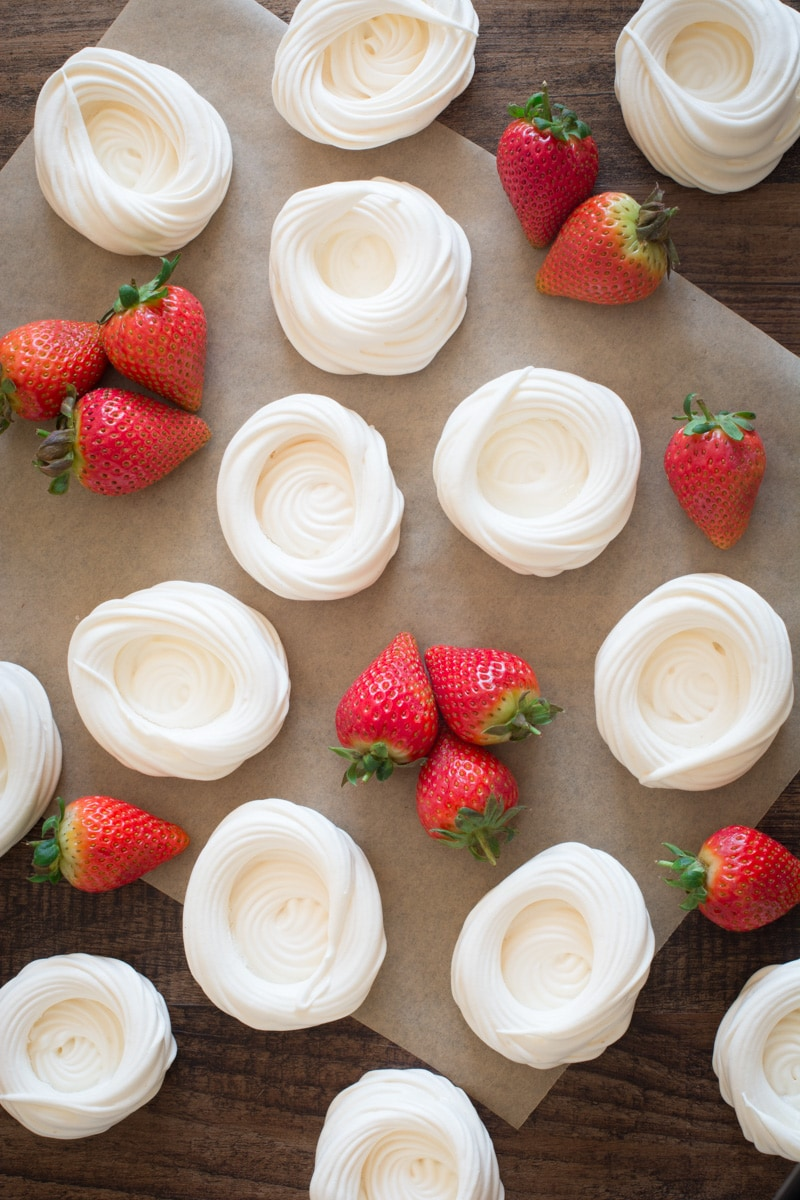 Looking down on lots of mini meringue nests surrounded by clusters of fresh strawberries.