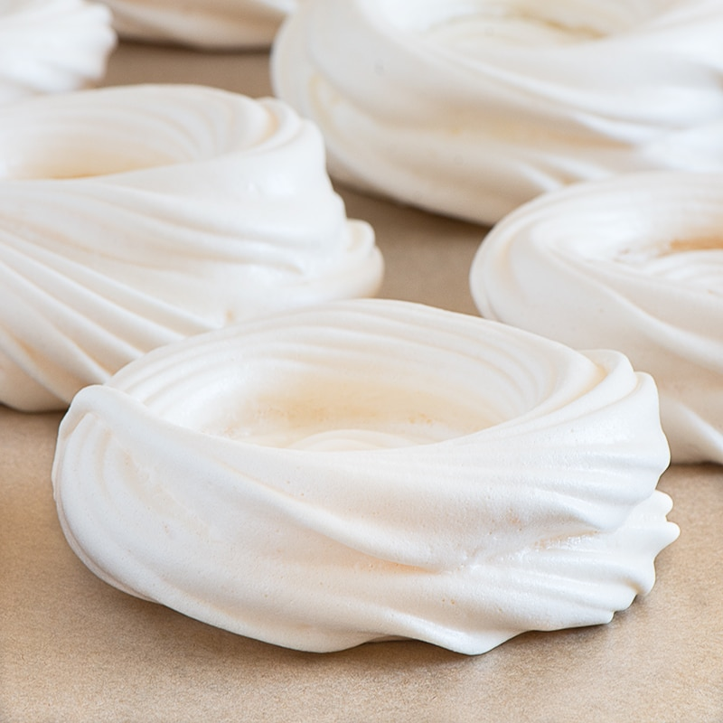 Unfilled meringue nests on a sheet of baking parchment.