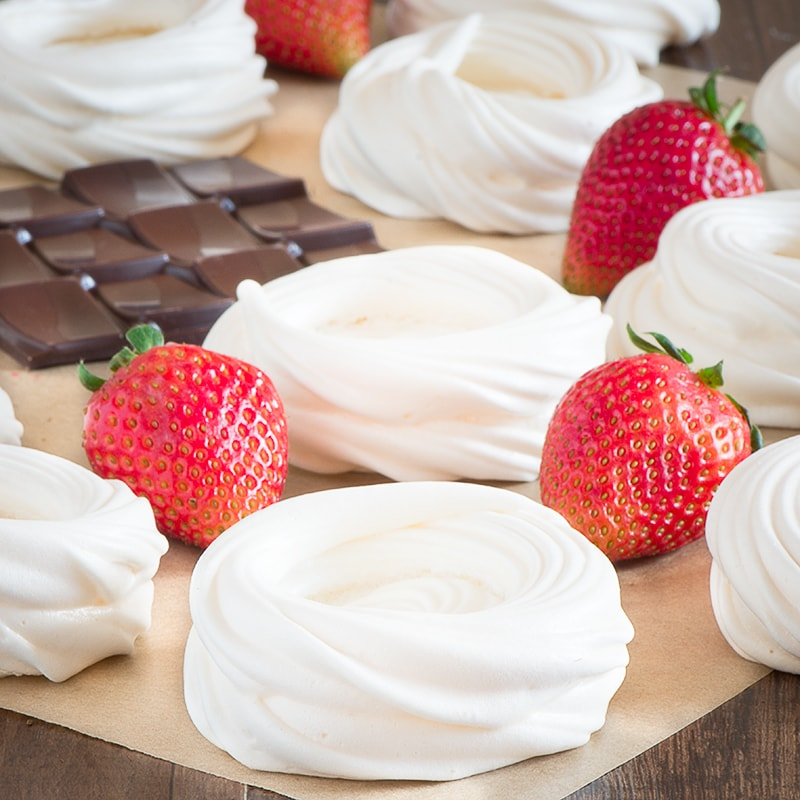 Meringue nests surrounded by fresh strawberries and a slab of dark chocolate.