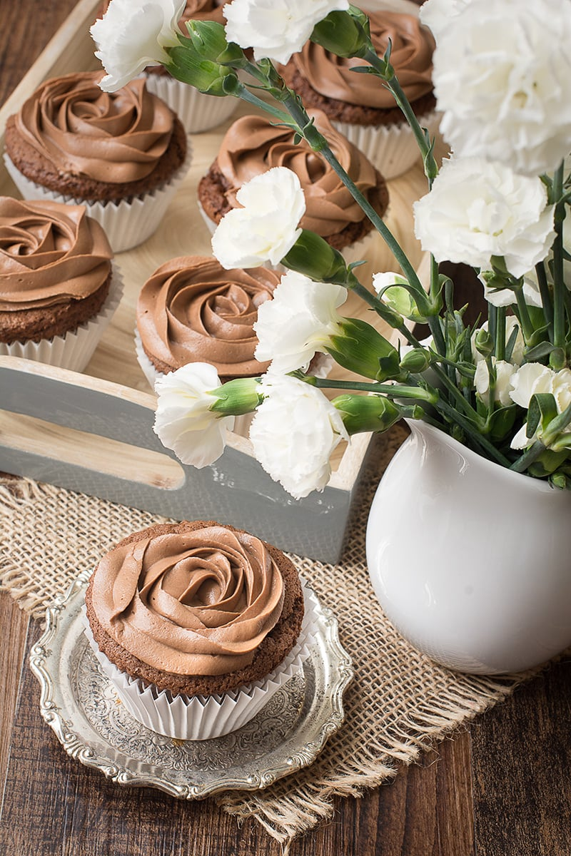 A Nutella cupcake topped with Nutella buttercream on a small silver dish next to a vase of white carnations. There's a tray of Nutella cupcakes in the background.