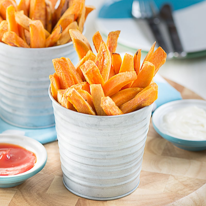 Two servings of the cooked fries stacked on their end in small metal post with ketchup and mayonnaise dipping bowls.