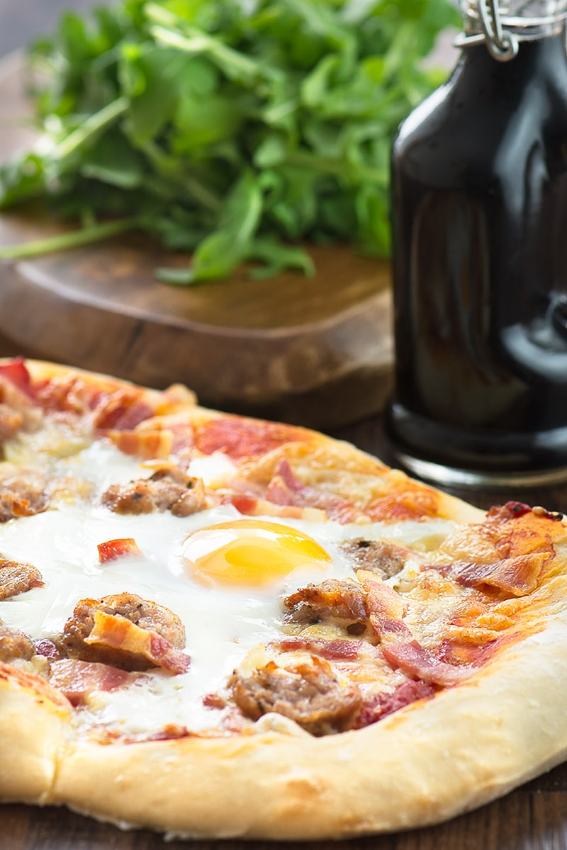 "All-day breakfast pizza - delicious homemade pizza dough topped with sausage, bacon, cheese and even a ""fried"" egg."