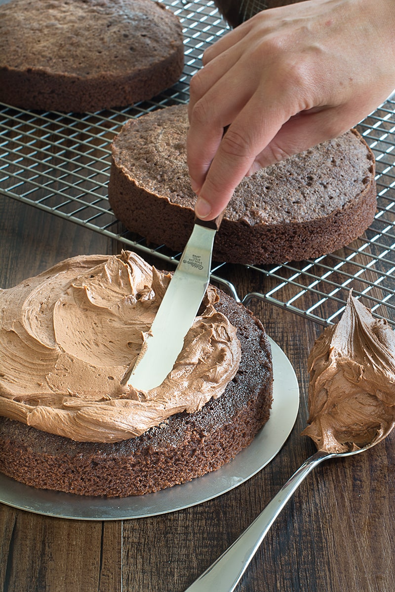 Spreading Chocolate Buttercream Onto A Round Birthday Cake Using Palette Knife There Are