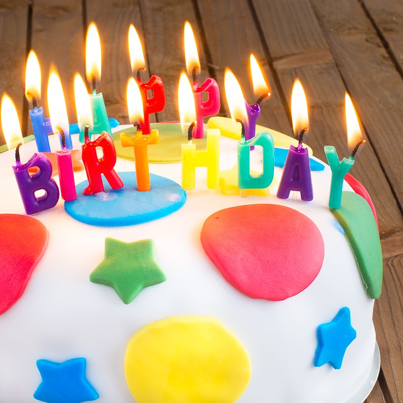 "A round birthday cake covered in white fondant icing decorated with multi-coloured stars and circles. The cake is topped with burning candles spelling ""HAPPY BIRTHDAY"""