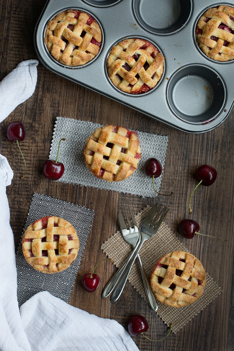 Homemade cherry pies with a pretty lattice top - crisp almond pastry, filled with juicy cherries. Perfect for a summer picnic or with a scoop of icecream for dessert.