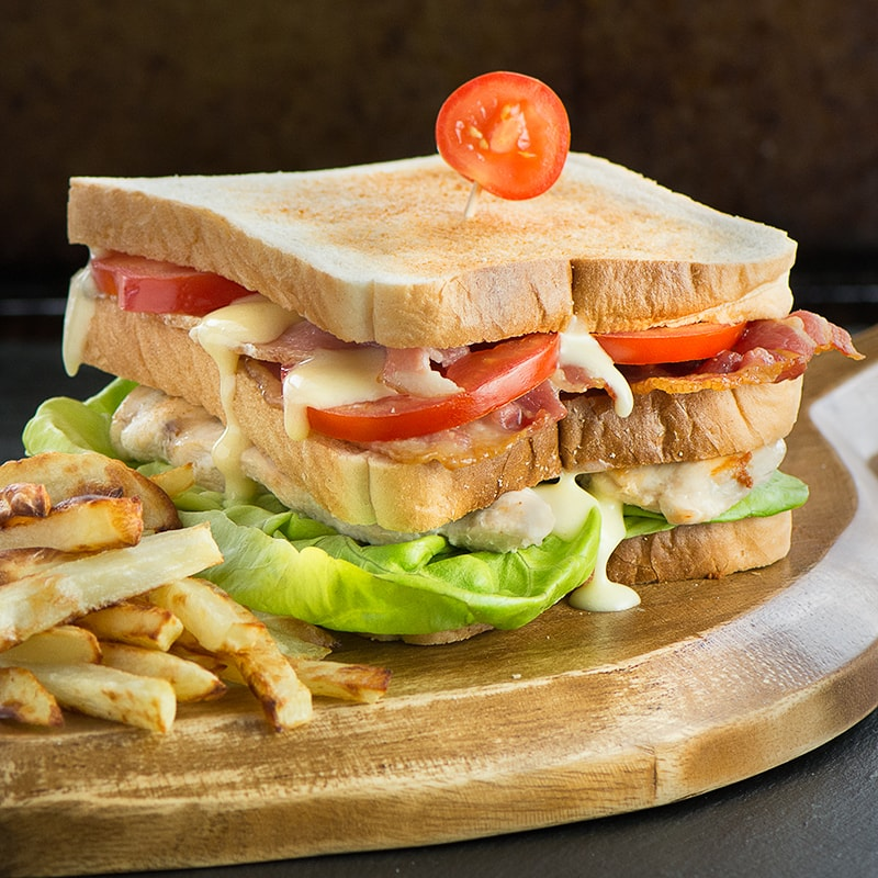 How to make the ultimate club sandwich - A double decker toasted sandwich with crispy bacon, succulent chicken, lettuce, tomato and delicious homemade mayonnaise.