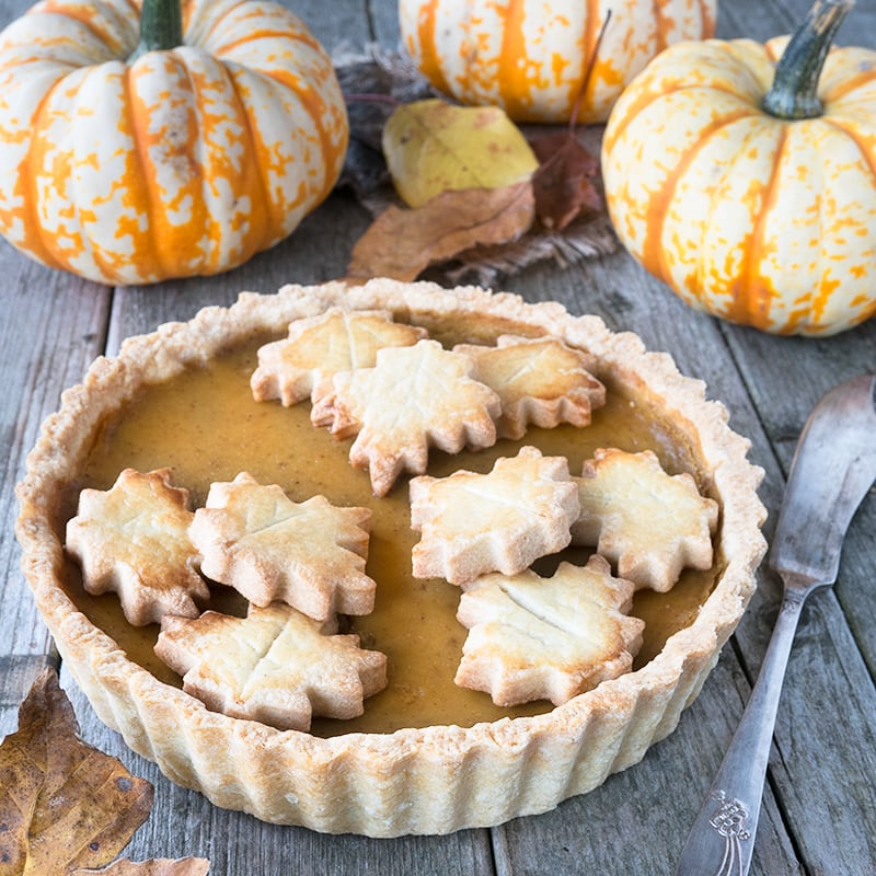 Angled view of a whole pumpkin pie decorated with pastry leaves on a wooden table with pumpkins in the background.