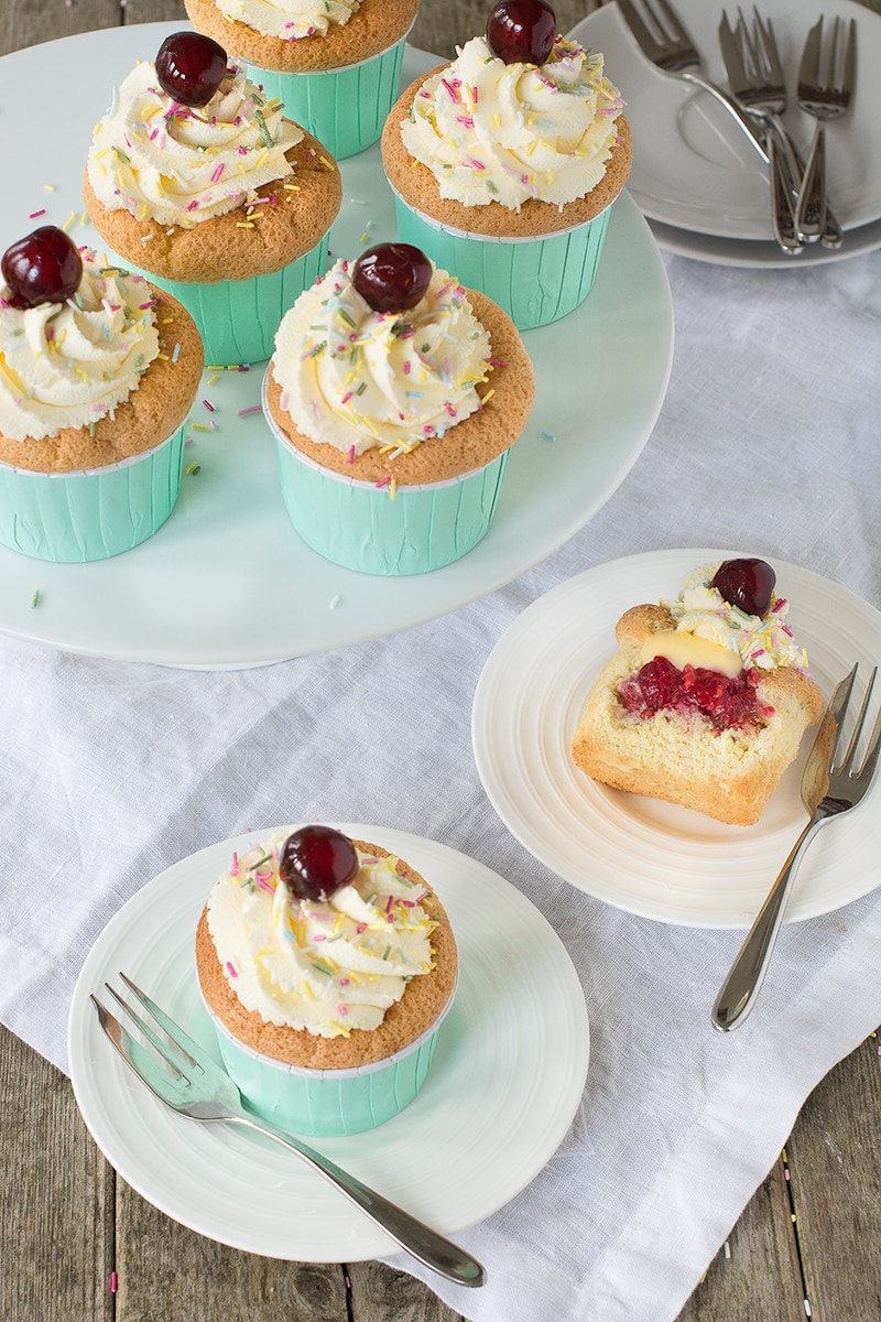 The classic dessert in cupcake form - Raspberry soaked sponge finger-style cupcakes filled with fresh raspberries and custard and topped with whipped vanilla cream.