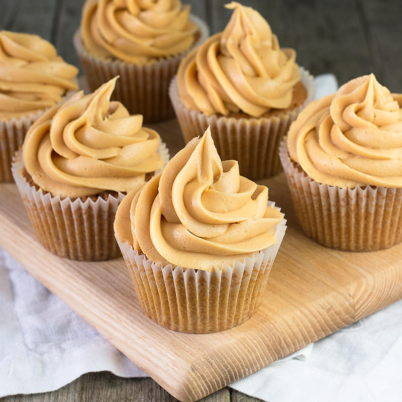 Six caramel cupcakes topped with caramel buttercream on a wooden board.