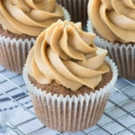 A close up of a coffee cupcake topped with a swirl of coffee buttercream on a cooling rack with more cupcakes behind.