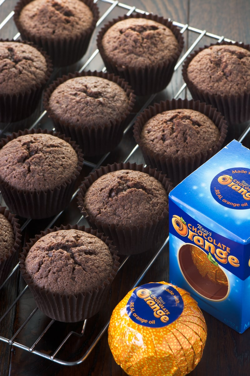 Chocolate orange cupcakes on a cooling rack with a box of chocolate orange at the side.