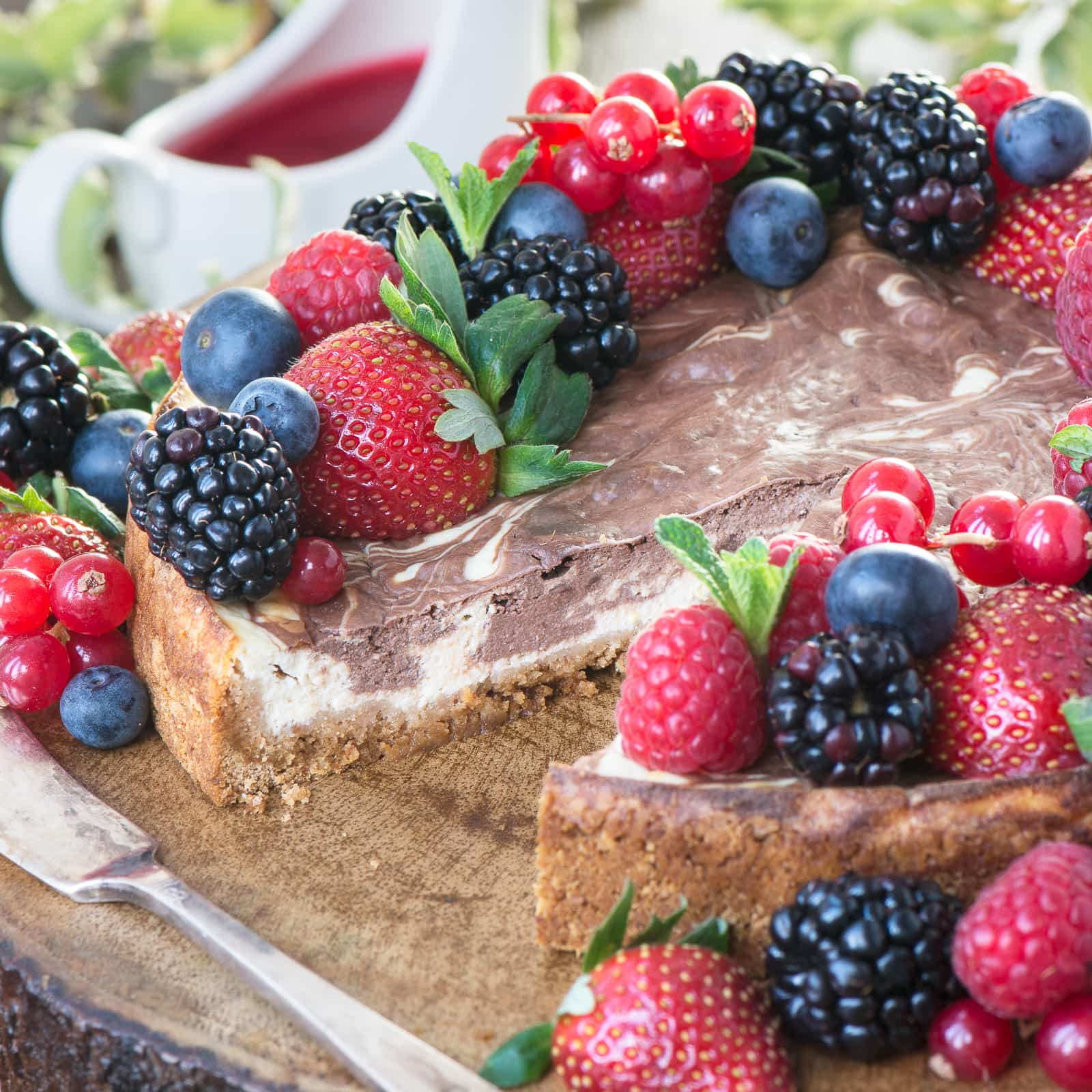 Baked chocolate marble cheesecake topped with fresh fruit with a slice removed.