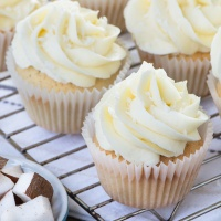 Coconut cupcakes iced with coconut buttercream on a cooling rack.