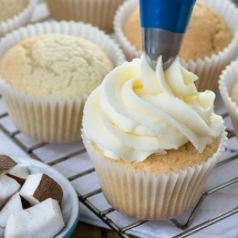 Coconut buttercream being piped onto a coconut cupcake.