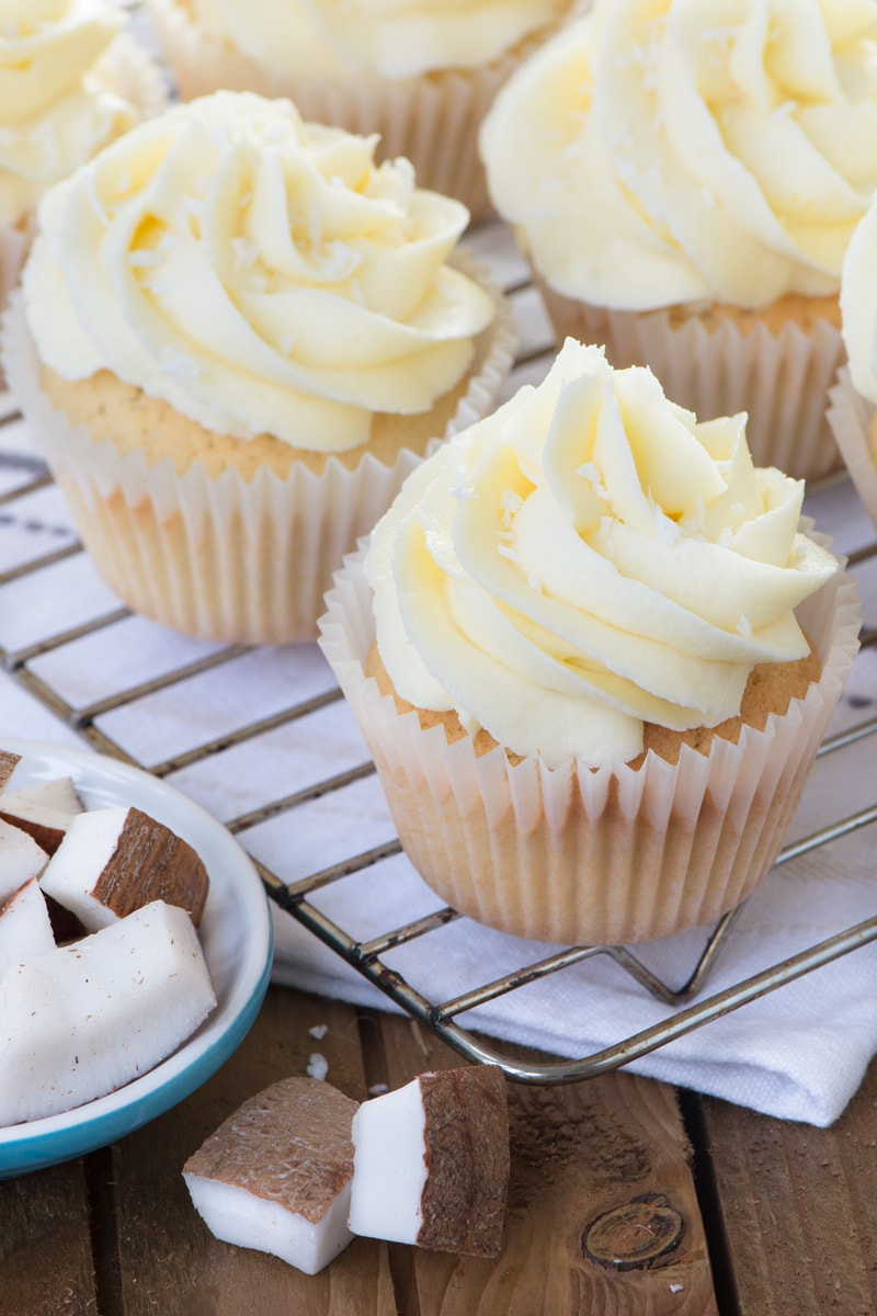 Coconut cupcakes decorated with coconut buttercream on a cooling rack.