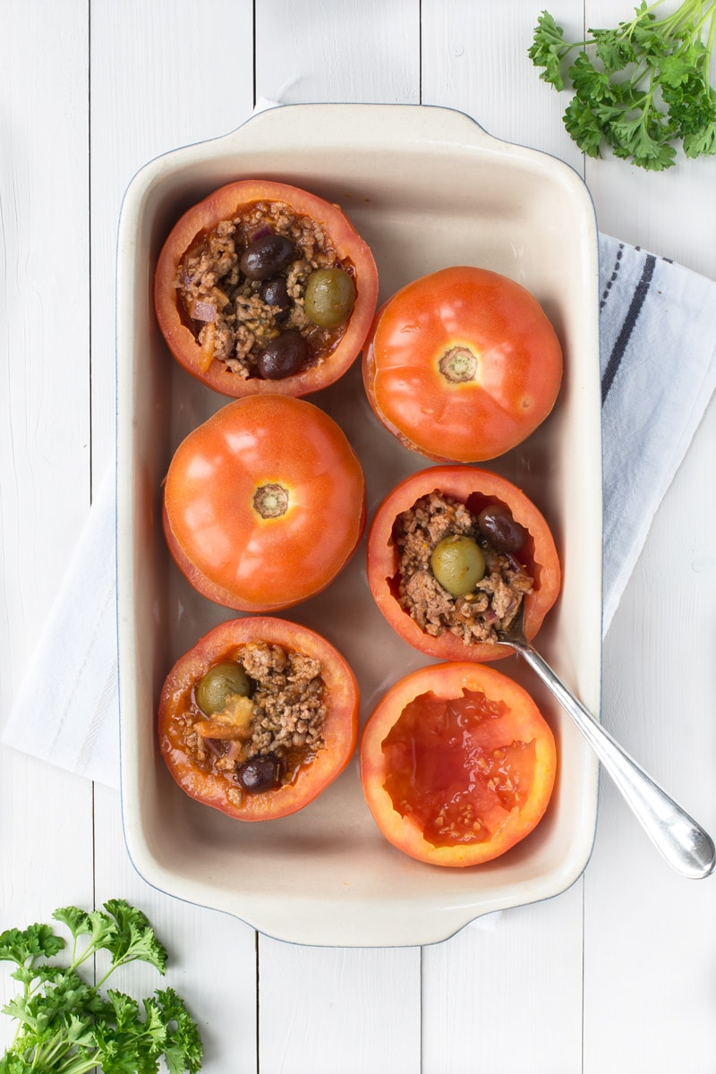 Mediterranean Lamb Stuffed Tomatoes in a baking tray - two filled with the tomato top on, two filled with the lamb filling showing with lots of olives, one showing the hollowed out tomato and one in the process of being filled with a spoon.