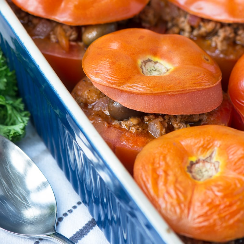A close up of Mediterranean Lamb Stuffed Tomatoes as they've just come out of the oven. The skin of the tomatoes is just starting to split indicating they're perfectly cooked. There's a spoon at the side ready for serving.