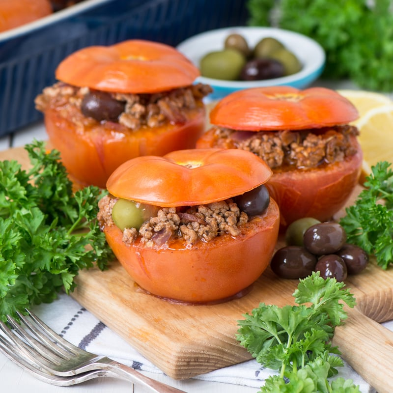 Three Mediterranean Lamb Stuffed Tomatoes on a serving board.