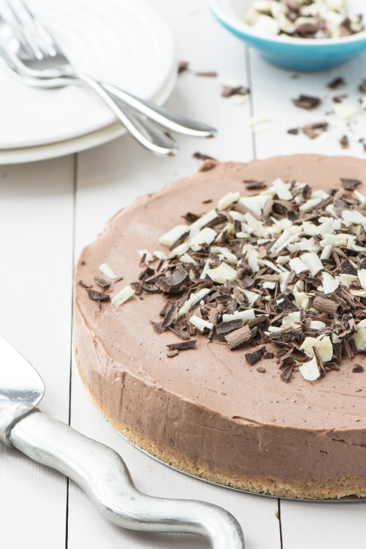 A no-bake chocolate cheesecake covered in white and dark chocolate curls next to a cake slice. There are white plates and cake forks and a pot of chocolate curls in the background.