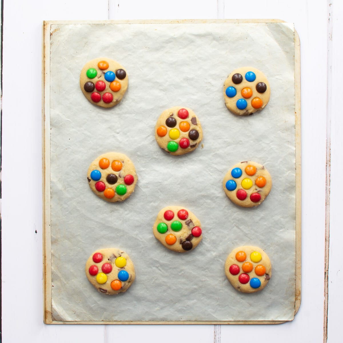M&Ms Cookies on the tray ready to bake. There's a large gap between the cookies to allow them to spread in the oven.
