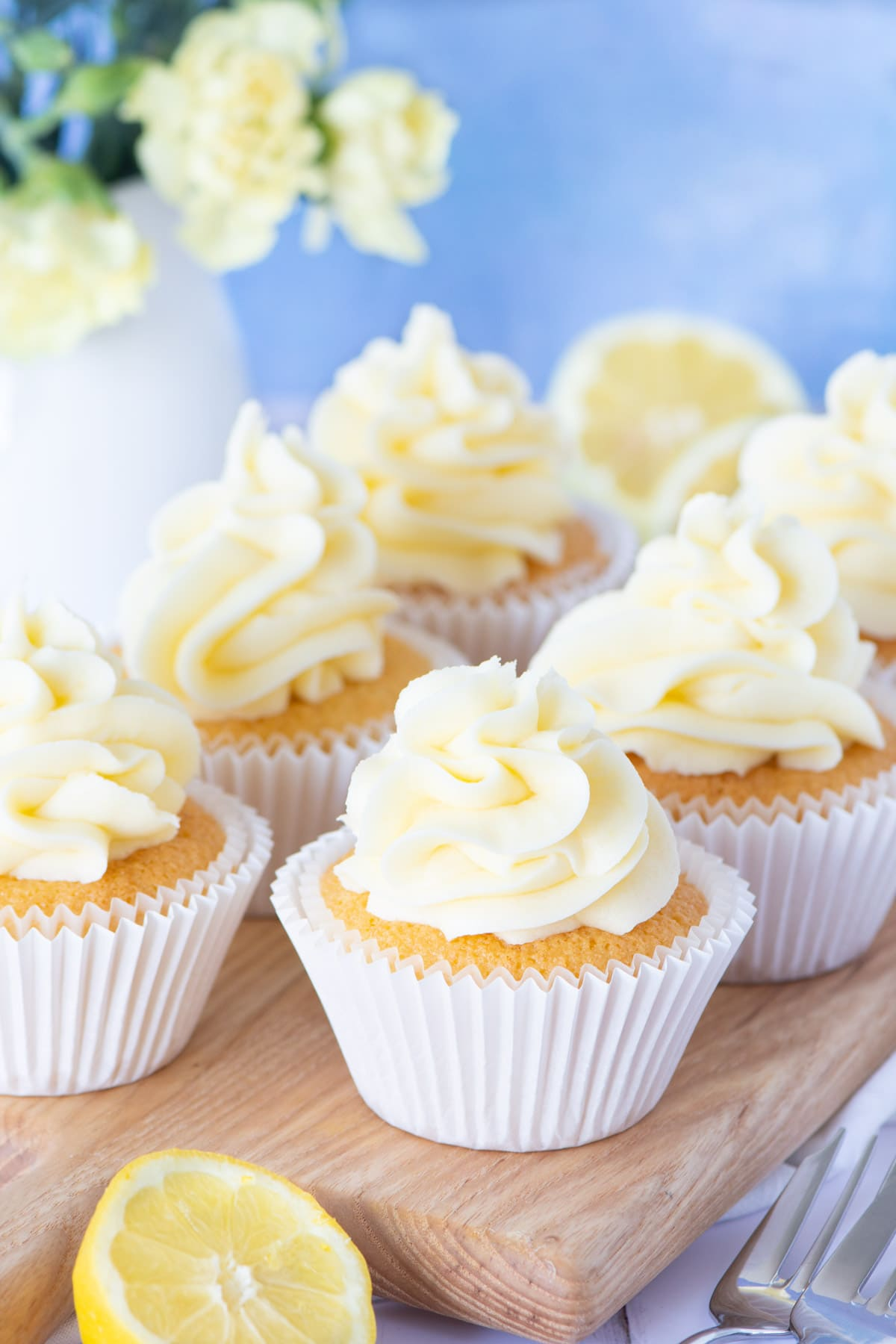 Six lemon cupcakes topped with swirls of lemon buttercream on a wooden board.