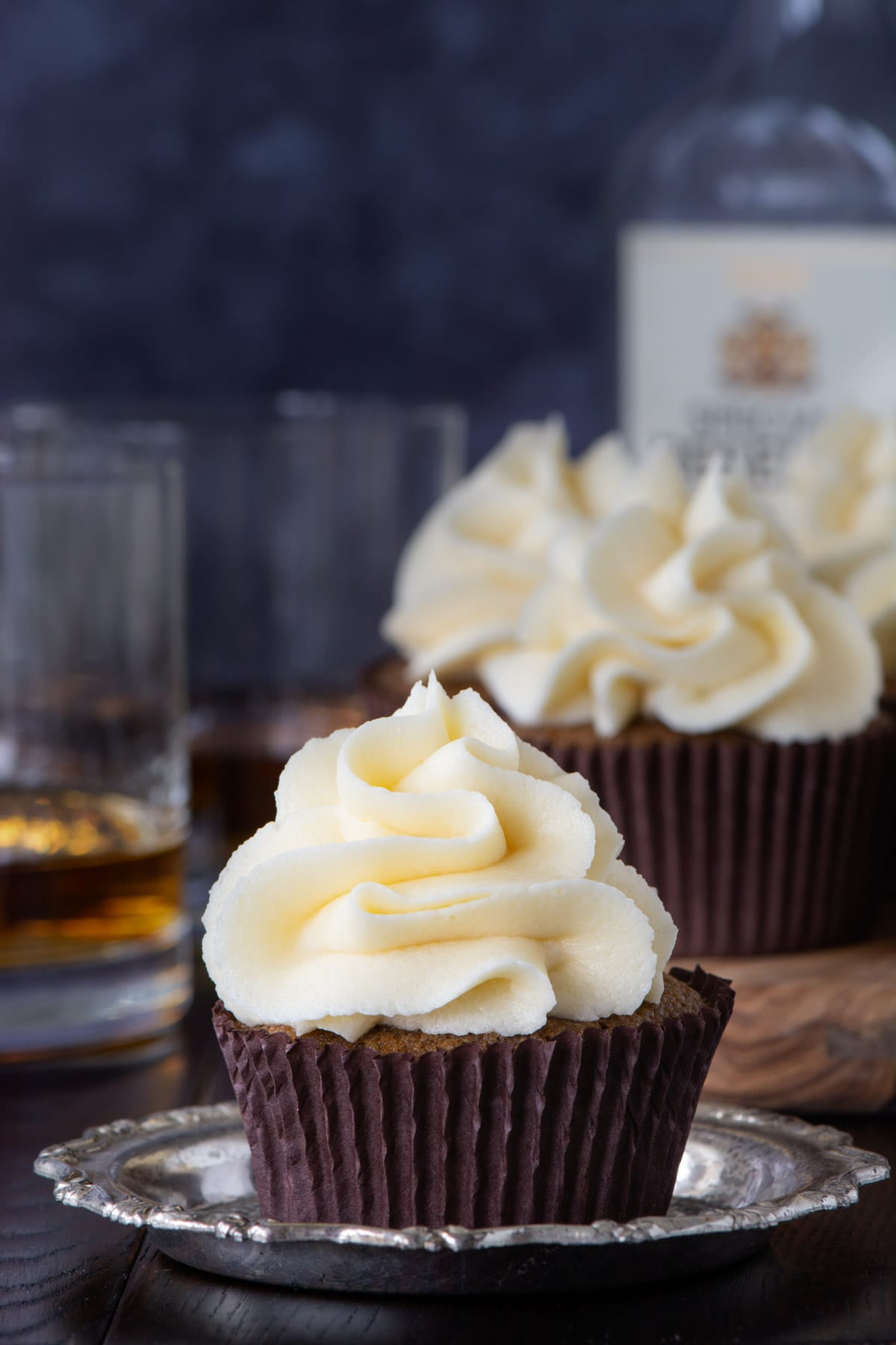 A close up of a coffee cupcakes topped with whiskey buttercream. There are more cupcakes in the background.