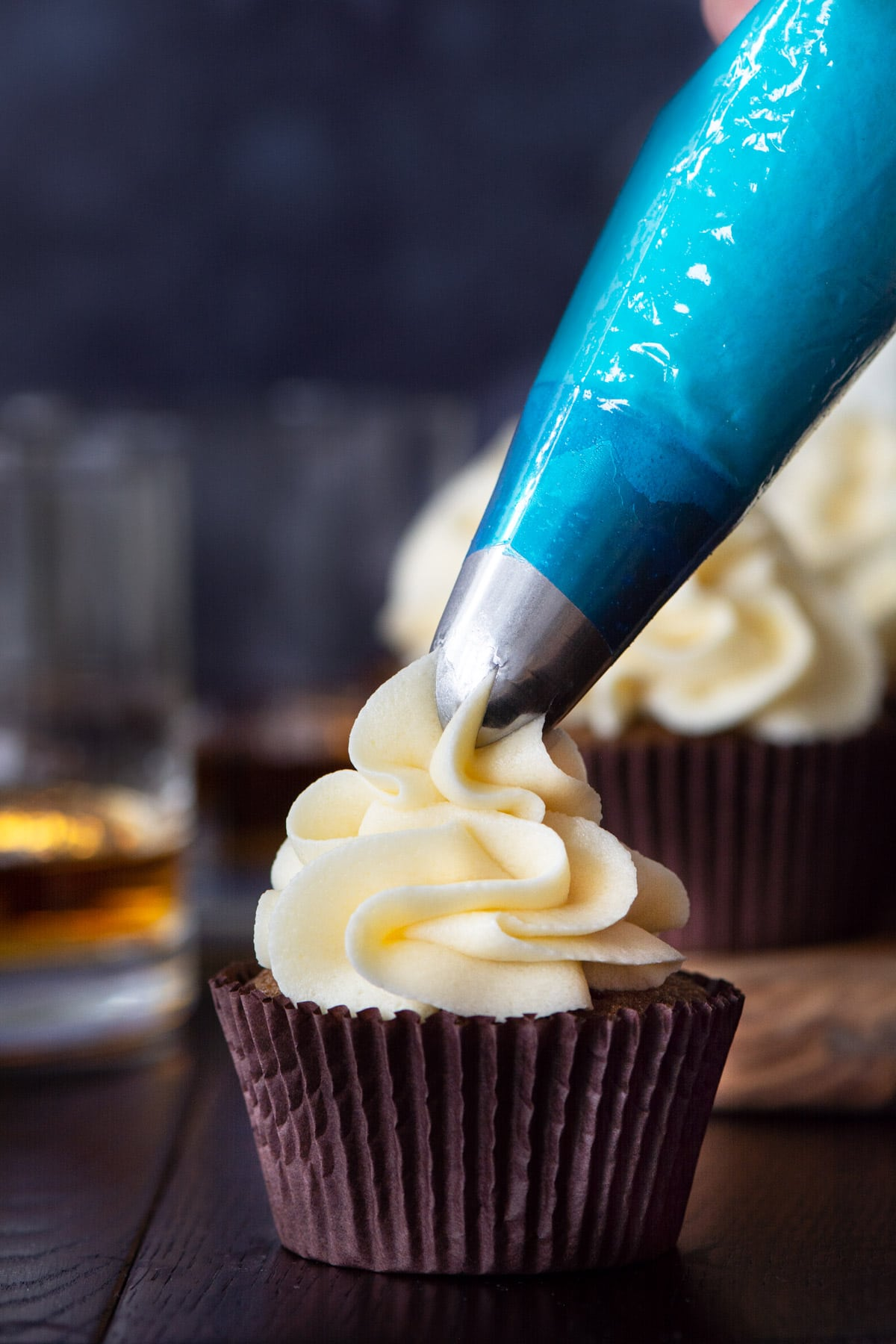 Whiskey buttercream being piped onto a cupcake.