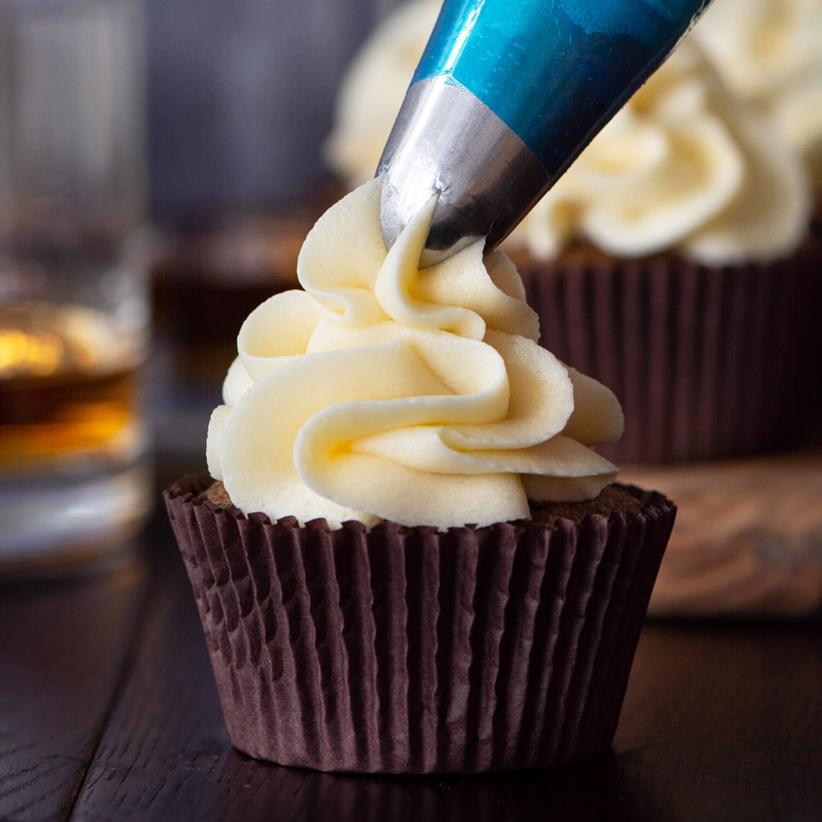 Whiskey buttercream being piped onto a coffee cupcake.