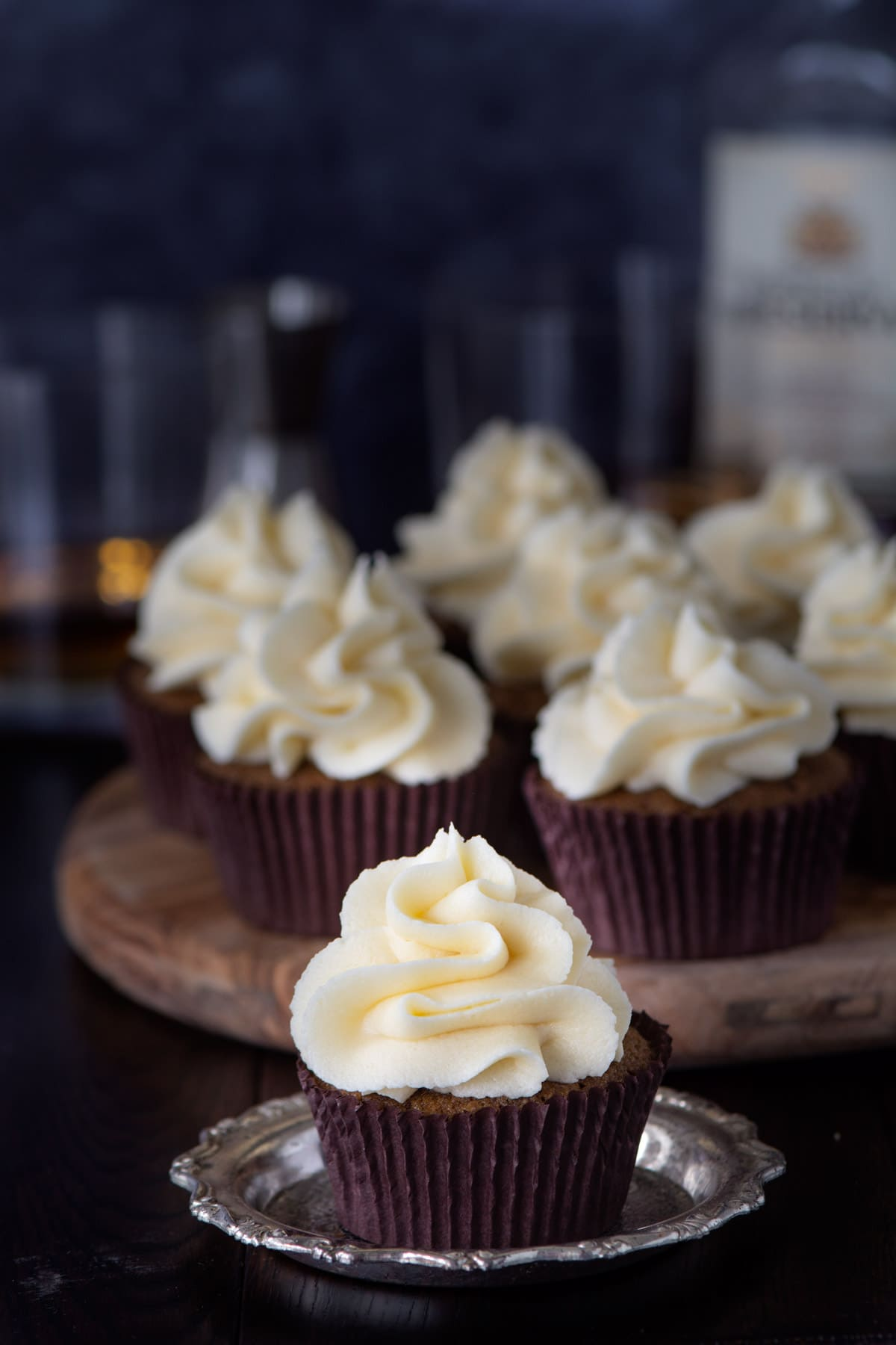 A coffee cupcake topped with whiskey buttercream. There are more cupcakes and a bottle and glasses of whiskey in the background.