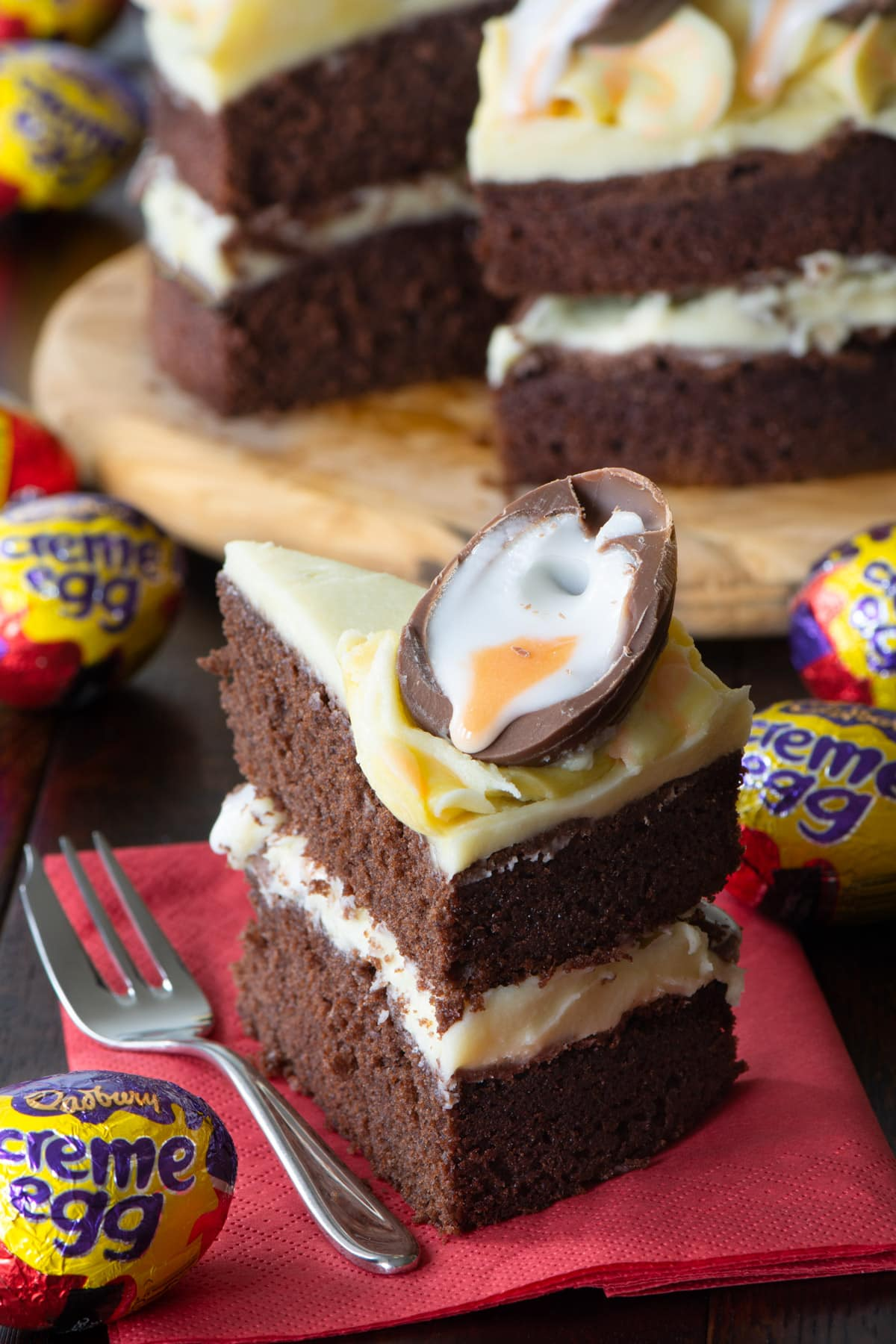 A slice of Creme Egg cake with the remaining cake in the background. A chocolate cake, with white chocolate buttercream, topped with Creme Egg halves.
