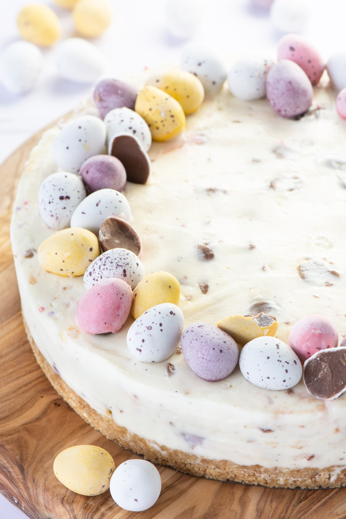 A white chocolate mini egg cheesecake topped with mini eggs. The eggs are arranged around the edge of the cheesecake. Some are broken to show the chocolate in the centre.