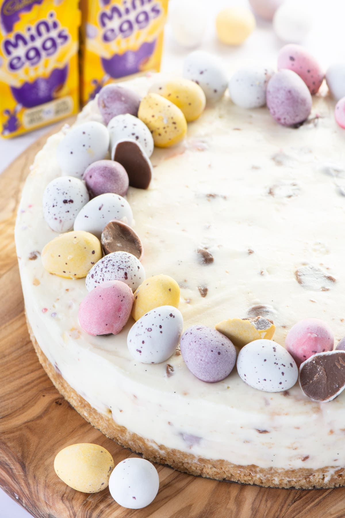 A white chocolate mini egg cheesecake with boxes of mini eggs in the background.