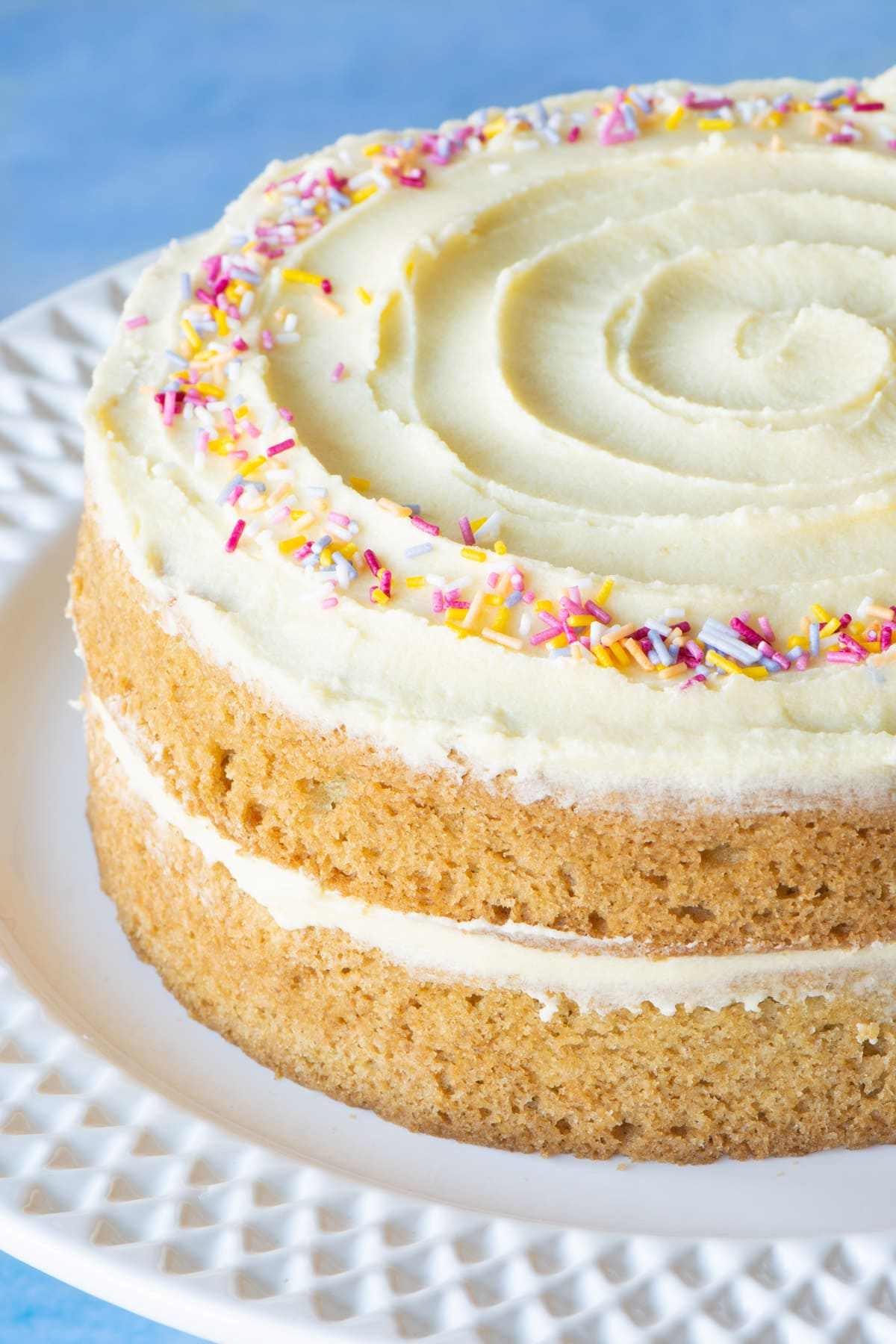 A vegan vanilla cake on a cake stand.