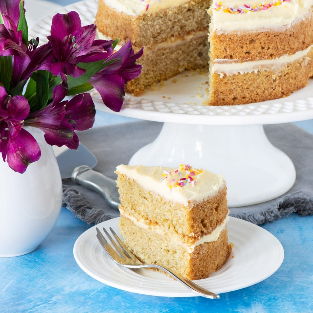 A slice of vegan vanilla cake with the rest of the cake in the background.