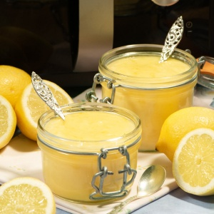 Two jars of lemon curd in front of a microwave.