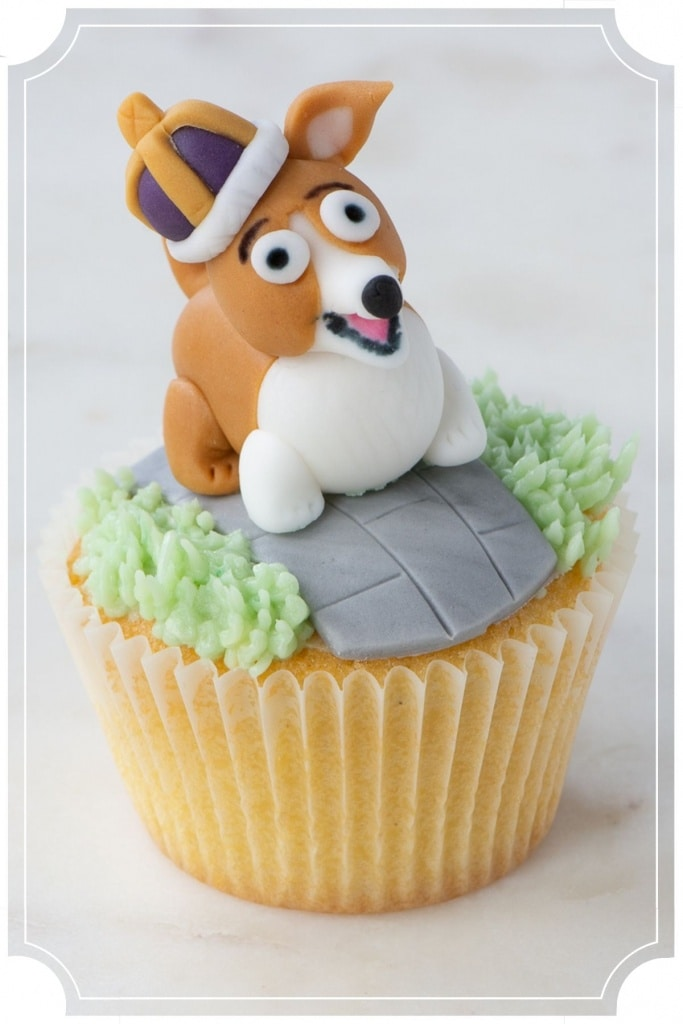 Cupcake topped with green buttercream grass, a fondant path and a fondant corgi wearing a crown.