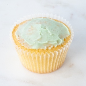 A cupcake topped with a thin layer of green buttercream.