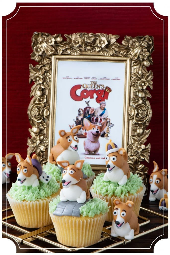 The finished Corgi Cupcakes decorated with buttercream grass, a fondant path and a fondant corgi. In the background is The Queen's Corgi DVD cover in a gold frame.
