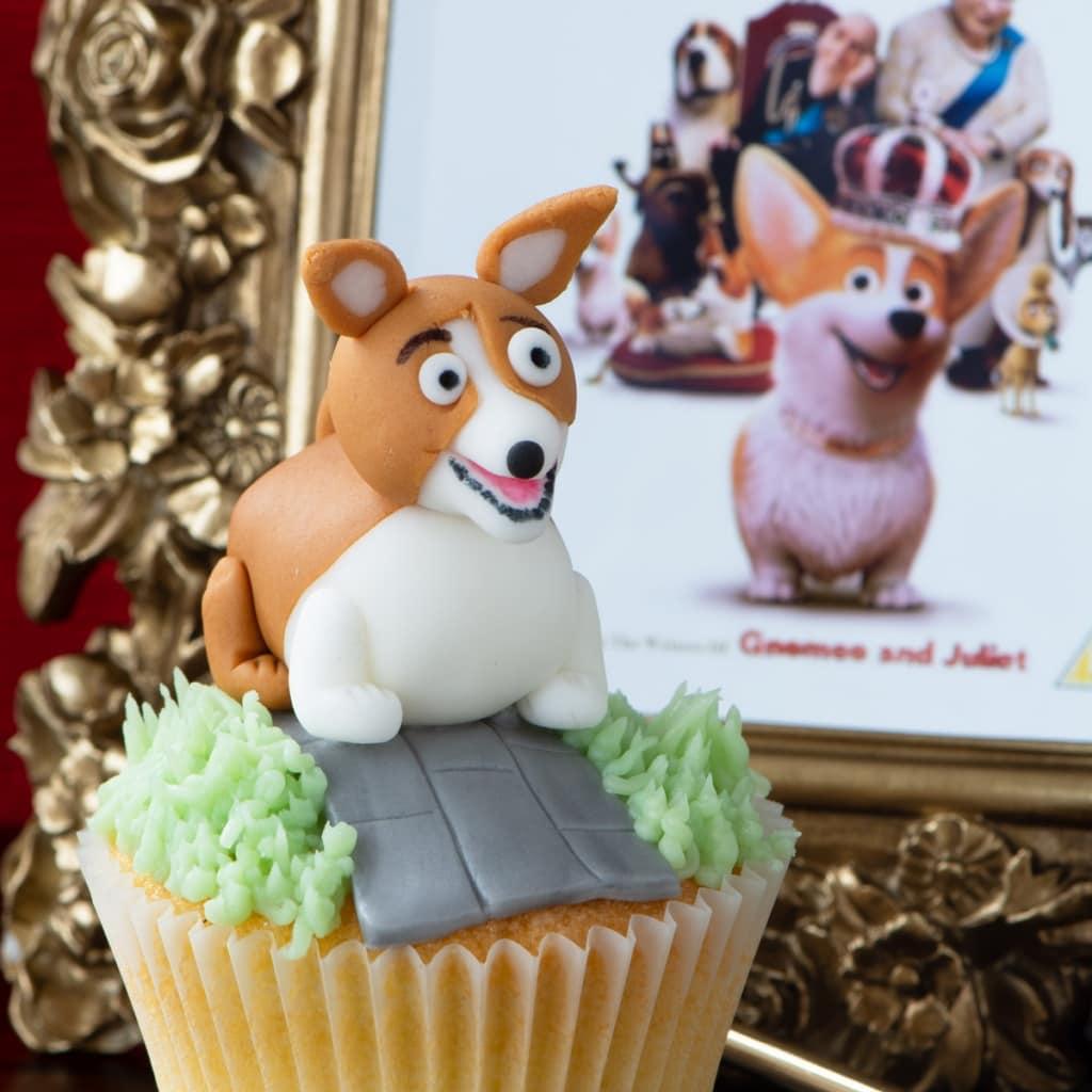 A fondant corgi cupcake with The Queen Corgi DVD cover in the background