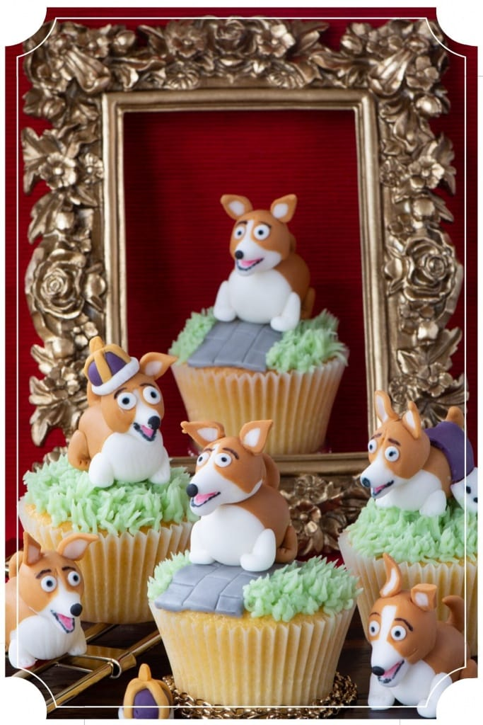 Corgi Cupcakes - Vanilla cupcakes topped with green buttercream grass, a fondant path and a fondant corgi. In the background one of the cupcakes in surrounded by a gold frame.